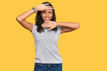Young african american girl wearing casual clothes smiling cheerful playing peek a boo with hands showing face. surprised and exited Wall mural