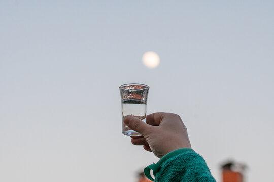 Junge Frau hält Schnapsglas in den Himmel am Abend mit Mond im Hintergrund