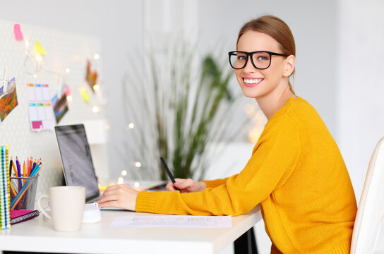 happy smiling freelancer woman in a yellow sweater works at computer at  workplace with Christmas lights.