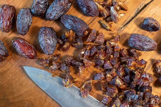chopping dried Medjool dates on cutting board flat lay