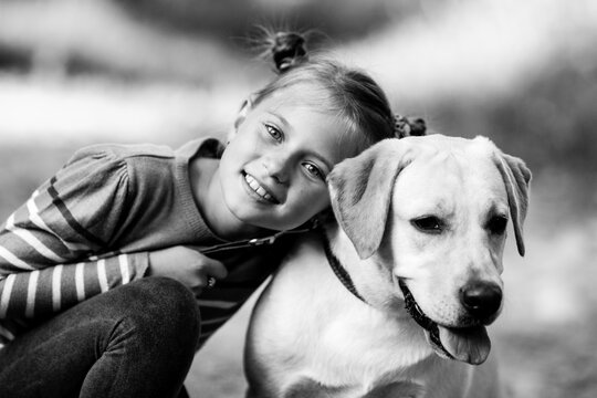 Ten-years-old girl with her dog. Black and white photo.