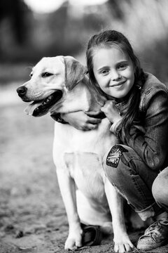 Portrait of a girl with her dog. Black and white photo.