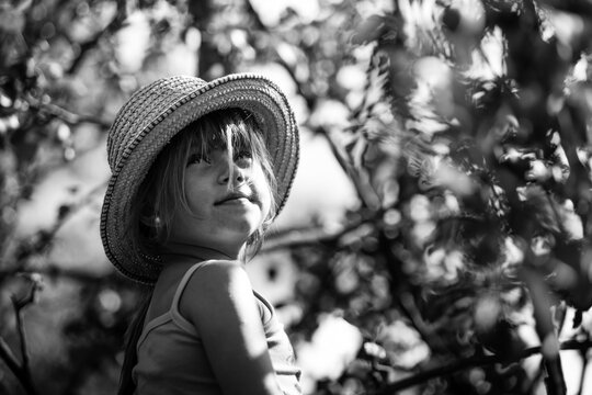 Little girl in a straw hat in the park. Black and white photography.