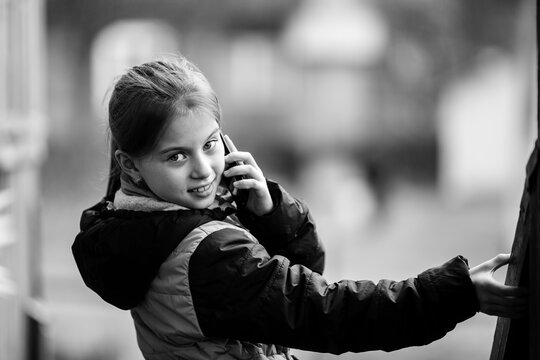 Little girl portrait, talking on mobile, outdoor. Black and white photography.