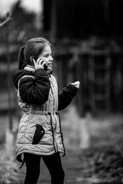 Little girl talking on the phone. Black and white photo.