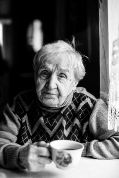 An old woman drinks coffee at home. Black and white photo.