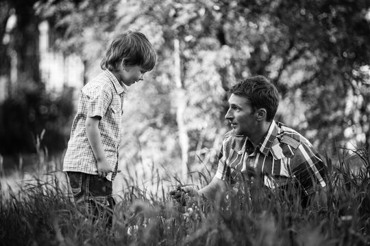 Young father and his little son playing on the park. Black and white photo.