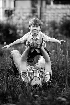Father playing with his small son in the grass. Black and white photo.