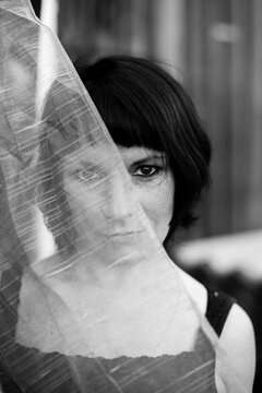 Woman outdoors, half of the face is covered by translucent veil. Black and white photo.