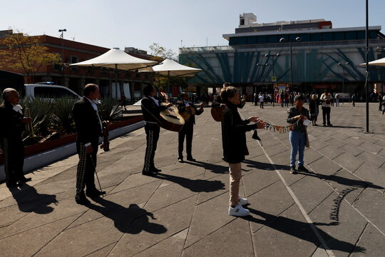 Mariachis play their instruments behind customers during the annual celebration of Saint Cecilia, the patron saint of musicians, as the coronavirus disease (COVID-19) outbreak continues, in Mexico City