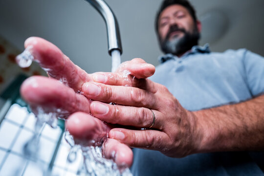 close up of man cleaning and washing his hands in the kitchen to kil germs and bacteria - preventing covid-19, coronavirus or any type of disease or flu