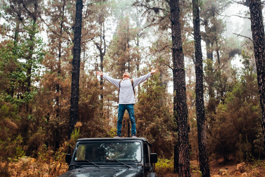one happy man enjoying nature and trees in the forest traveling with his car or vehicle having fun