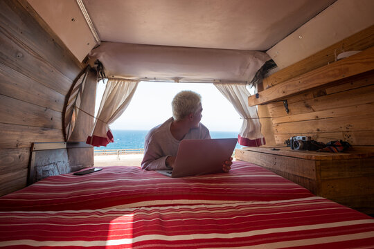 inside view of a minivan with a young blonde man using his laptop and working near of the beach and the sea - traveler and nomad people lifestyle having fun