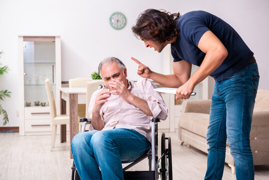 Old man in wheel-chair and young bad caregiver indoors