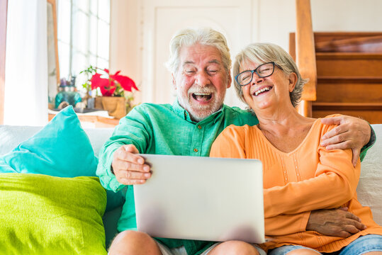 couple of two happy mature and old people or seniors at home sitting on the sofa enjoying and having fun laughing together looking and using a laptop or computer pc