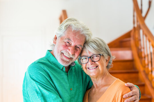 portrait and close up of two happy seniors or mature and old people smiling and looking at the camera - couple of pensioners having fun at home