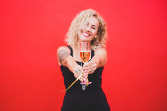 portrait beautiful curly woman celebrating new year 2021 smiling and looking at the camera holding a glass or cup with champagne