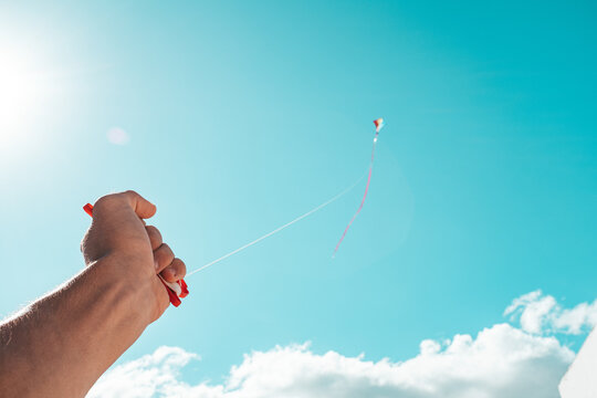 close up of hand holding and playing with a flying kite in the colorful sky