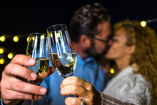 close up of hands of two happy and in love people holding their glass with champagne and kissing at the background for the new year 2021