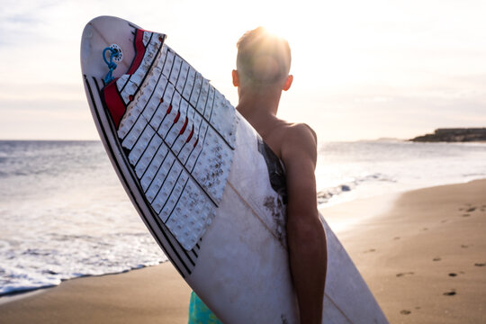 close up of man running on the beach with his surfboard going surfing at summer with the sunset