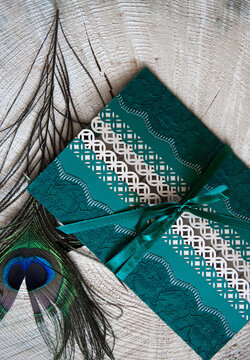 High Angle View Of Wedding Invitation With Peacock Feather On Wooden Table