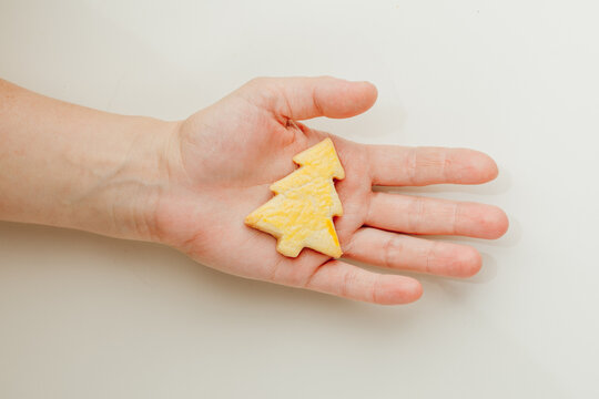 woman holding a Christmas tree cookie in hand