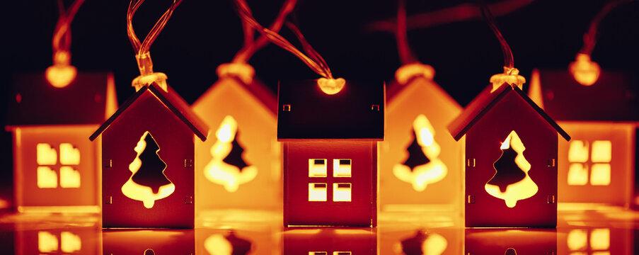 house and Christmas tree shape garlands, illuminated glow light at night