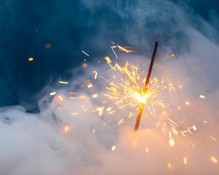 fire sparkler in dense smoke, abstract Christmas firework background