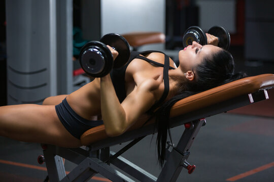 Athletic young woman brunette in sportswear is doing a dumbbell press on inclined bench at gym