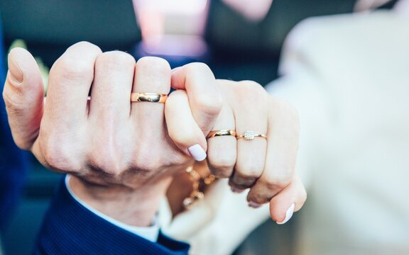 Cropped Image Of Bride And Groom With Rings Connecting Fingers During Wedding