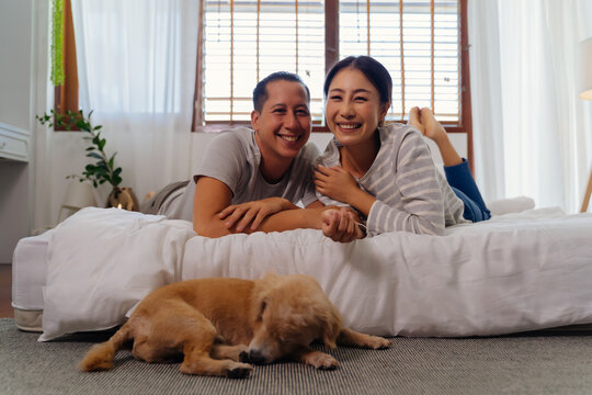 Portrait of happy young adult Asian couple looking at camera on bed together with dog pet in bedroom interior scene. 30s mature husband and wife smiling with happiness. Happy relationship life concept