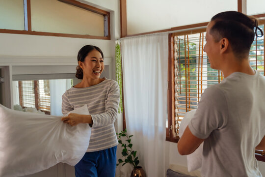 Portrait of young adult Asian couple playing pillow fight in bedroom interior scene. 30s mature husband and wife smiling and having a fun activity. Marriage and happy relationship life concept