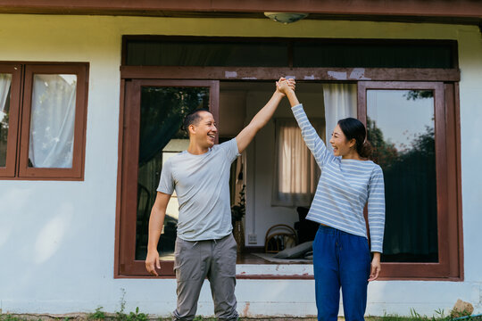 Portrait of young adult Asian couple holding hands up together with home interior in background. 30s happy mature husband and wife smiling. Property and real estate achievement concept