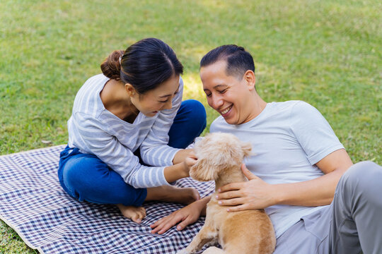 Young adult Asian couple playing a puppy with green grass outdoors in background. 30s mature man and woman lying down on mat in the park touching a dog pet. Happy family and modern life concept
