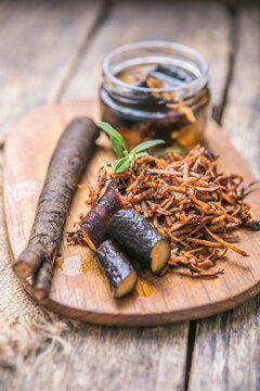 Comfrey root ( Symphytum)  on a table with honey collected in spring, on a table