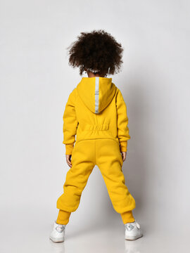 Curly mulatto dark-skinned kid girl in warm blue sports jumpsuit with hood and sneakers stands back to camera over white wall background, rear view. Trendy children fashion, stylish outfit