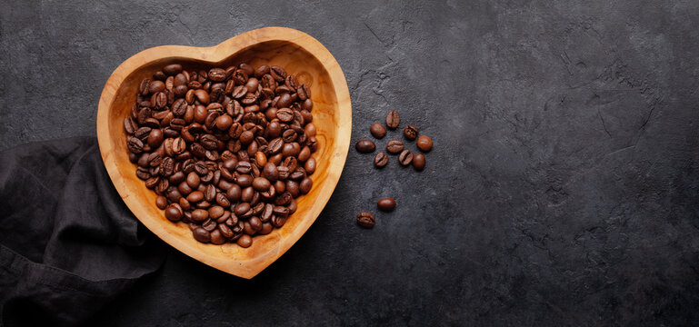 Roasted coffee beans in heart shaped bowl
