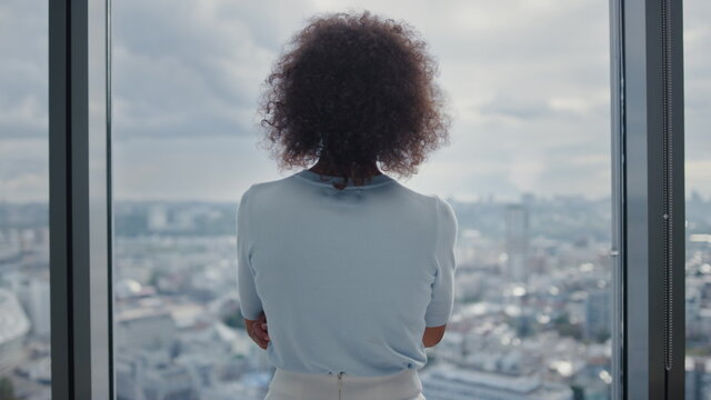 Businesswoman standing at window in office. Entrepreneur enjoying city view