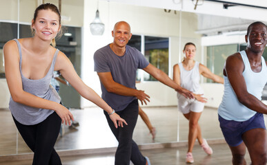 happy active dancing people practicing vigorous swing in dance studio