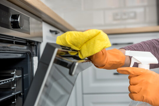 Man's hand in gloves cleaning the kitchen oven