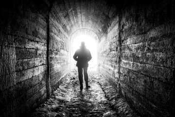 The man walks down the tunnel towards the light. Fotomurales