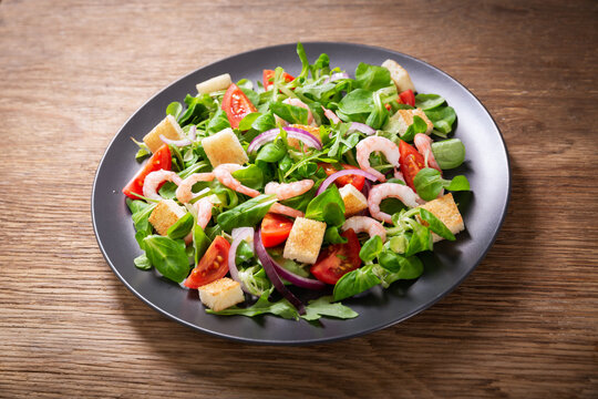 plate of fresh salad with shrimps, greens and tomato