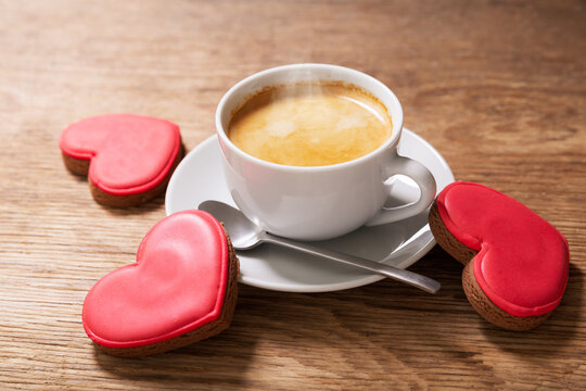 Valentines day.  Cup of coffee and colorful heart shaped cookies