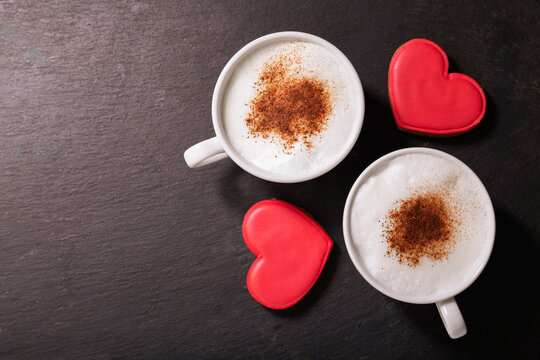 Valentines day.  Cups of cappuccino coffee and colorful heart shaped cookies on dark background,