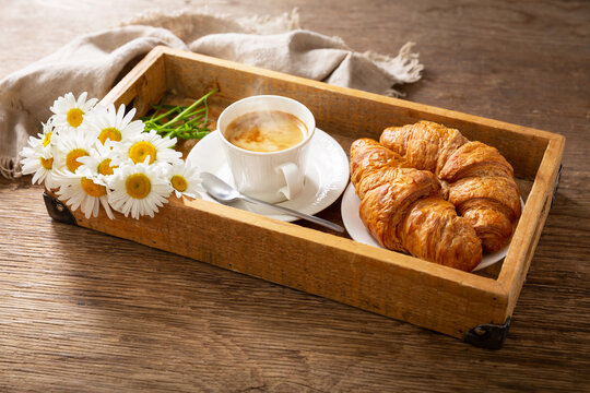 cup of coffee, croissants and daisy flowers on a tray