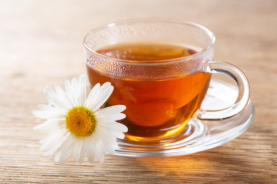 cup of herbal chamomile tea with fresh chamomile flower