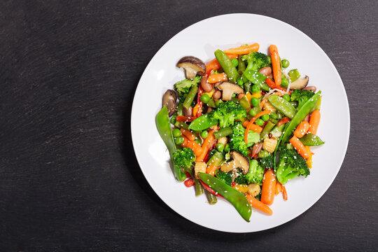 plate of stir fried vegetables on dark background