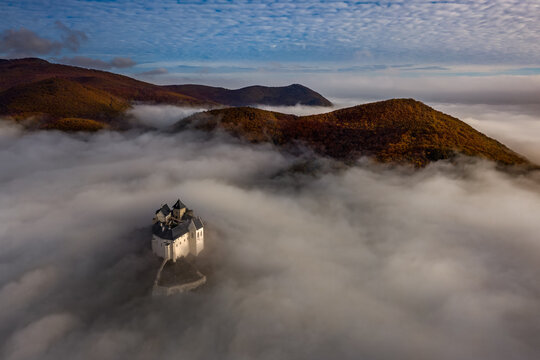 Fuzer, Hungary - Aerial panoramic view of the beautiful Castle of Fuzer standing out of the fog on an autumn morning with Zemplen Mountains and cloudy blue sky at background