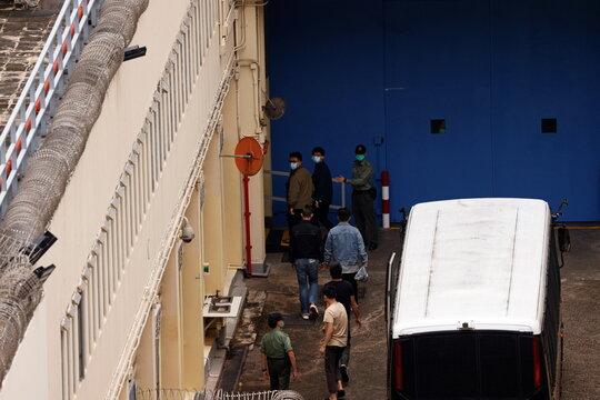Pro-democracy activists Ivan Lam and Joshua Wong arrive at Lai Chi Kok Reception Centre by prison van in Hong Kong