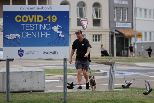 A man walks his dog near a COVID-19 testing centre at Bondi Beach in Sydney